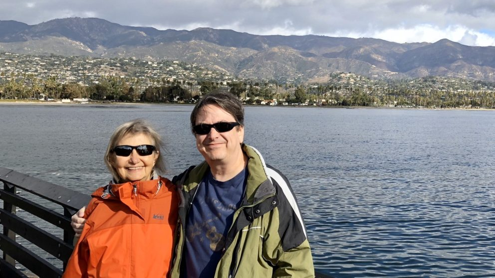 Scott and his aunt pose in front of water and hills in Santa Barbara, California.