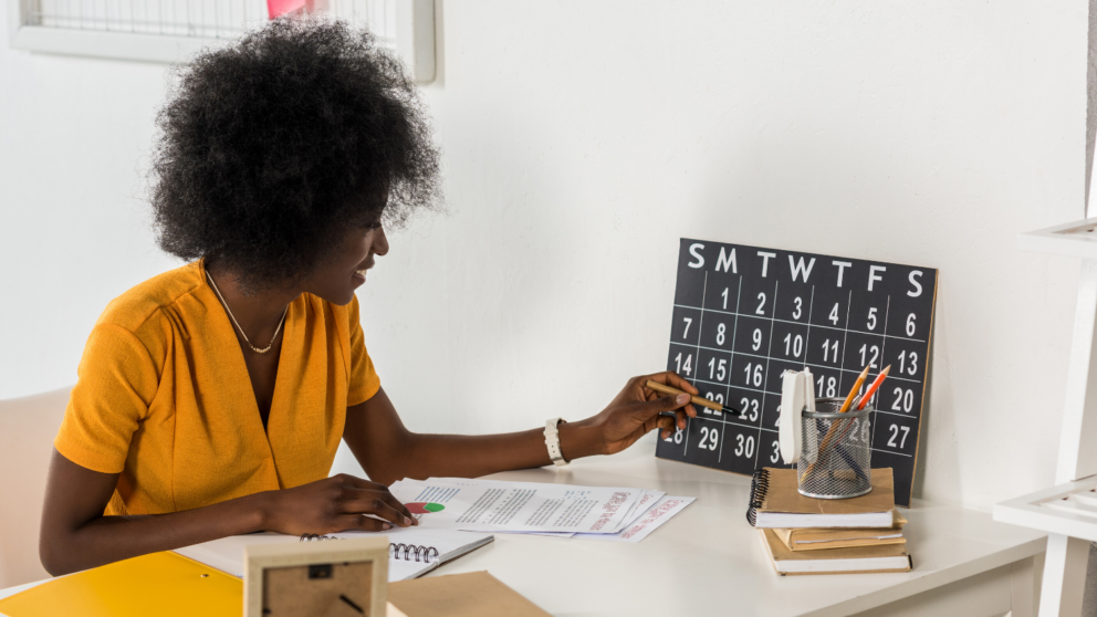 Woman at a desk looking at a calendar on the wall.
