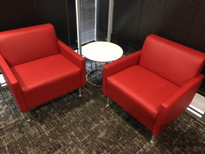 Two red armchairs with a round white table situated in between.
