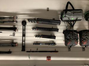 Backpacks, tripods, extensions and other production equipment hands neatly on a white wall.