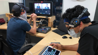 Two men wearing masks and headsets watch recorded footage at a desk in the instructional media production control room.