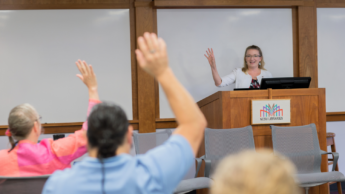 Associate Vice Provost for Academic Technology Innovation Donna Petherbridge welcomes faculty at the 2018 Summer Shorts in Instructional Technologies program. Petherbridge stands at front of room interacting with faculty. Faculty have hands raised.
