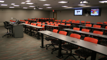DELTA Classroom with red rows of seats and a computer podium.