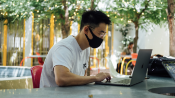 man with mask on computer