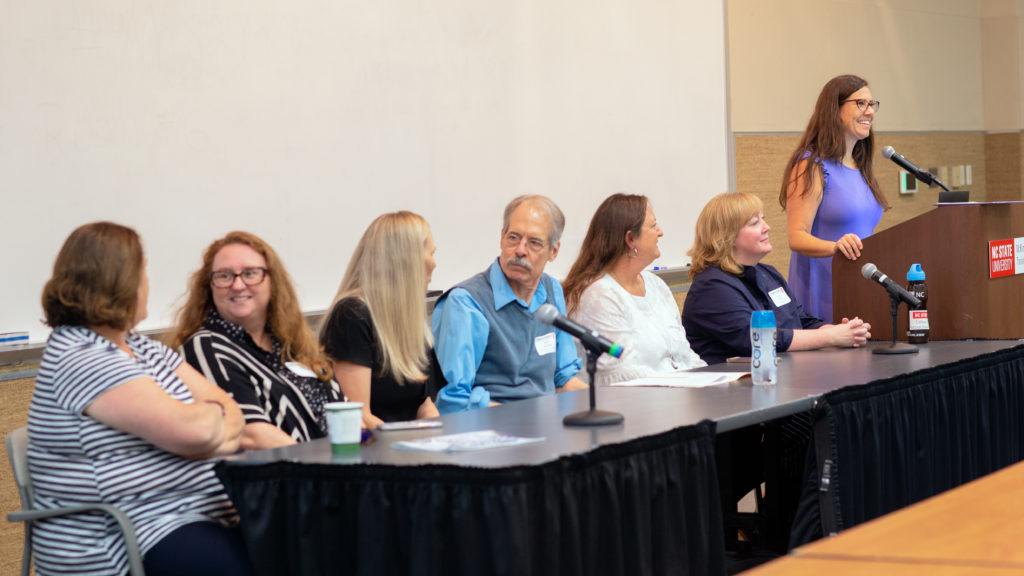 Bethanne Tobey stands at a podium before a panel discussion of faculty members. The faculty are seated at a table beside her.