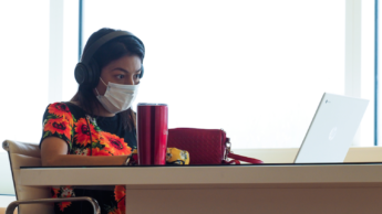 Person sits at a table with mask, headphones and a laptop