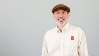 Portrait of David Howard against a white background. He is pictured wearing an NC State shirt and a brown hat.