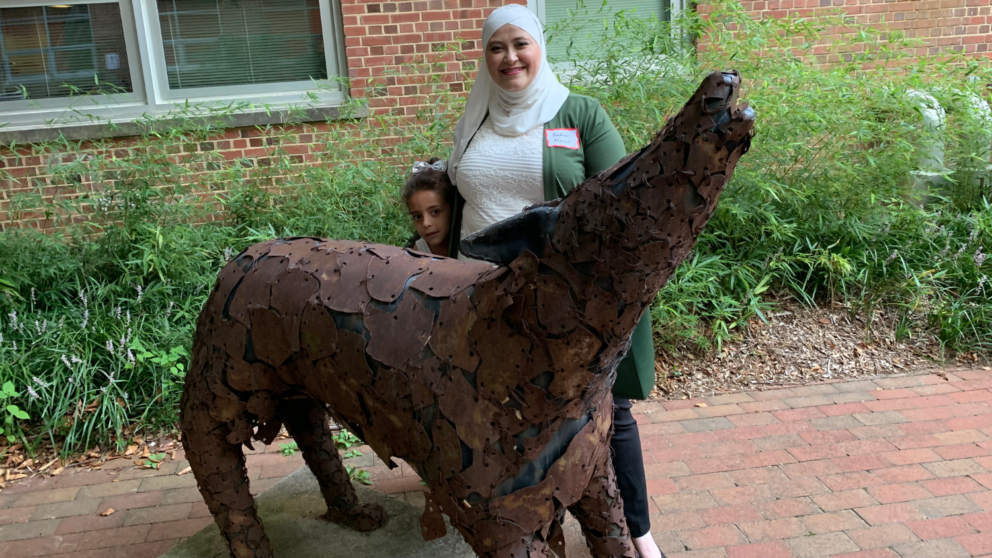 Gadeer and a child pose with a metal wolf statue outside of Nelson Hall.