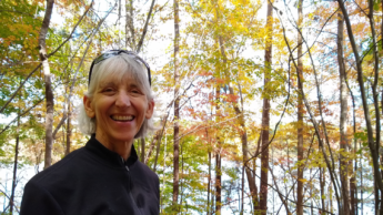 Annette Moore smiles in front of woods and a lake view.