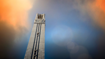The NC State belltower against a blue and orange sky.