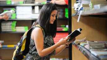 Student quickly views book in a bookstore.