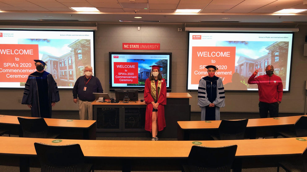 Five people stand physically distanced in a classroom. Projectors and a television display the SPIA 2020 Commencement Ceremony