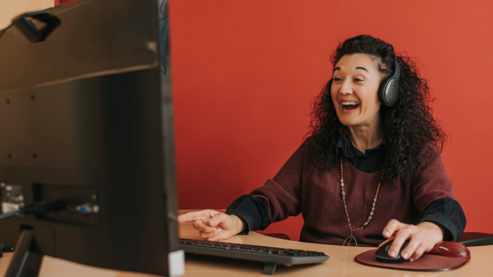 Woman sits in front of computer screen at desk and smiles/laughs.
