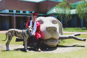 Hunter Everett with a dog in graduation attire in front of the NC State CVM dog statue