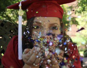 Kathy Nowak blows confetti in graduation attire.