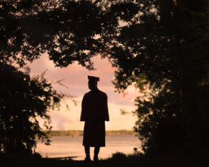 Silhouette of graduate surrounded by trees.