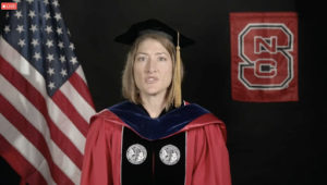 Christina Koch speaks in graduation attire in front of an American flag and an NC State flag.