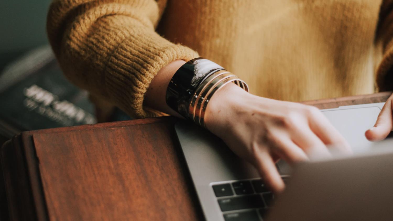 Hands typing across a laptop's keyboard.