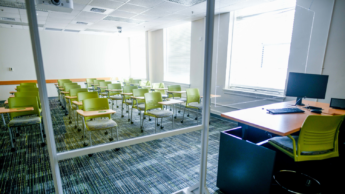 Empty NC State classroom with green seats.