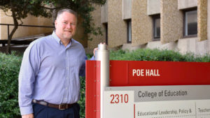 Kevin Oliver stands beside the Poe Hall, College of Education sign.
