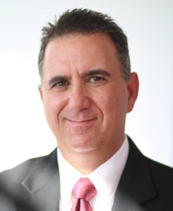 Peter Koutroumpis wearing black suit and red tie in headshot.