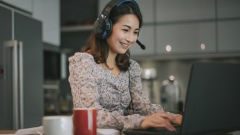 Woman smiles while working on computer and wearing a headset.