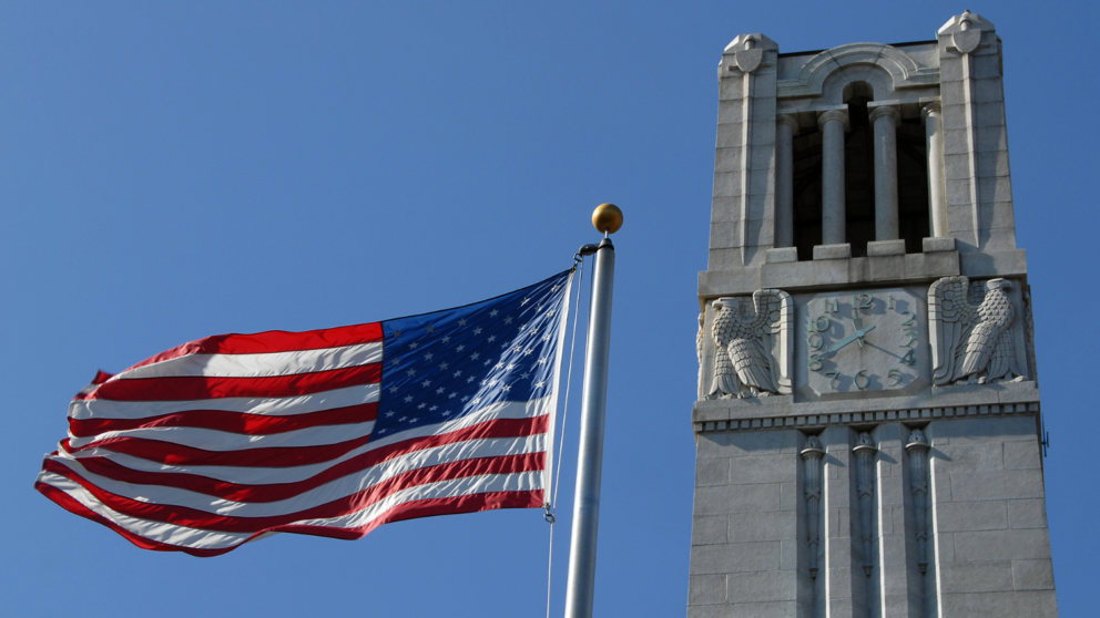 NC State belltower and the American Flag.