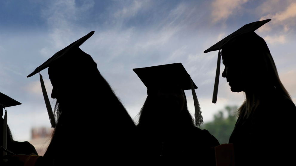 Silhouette of graduates wearing their caps