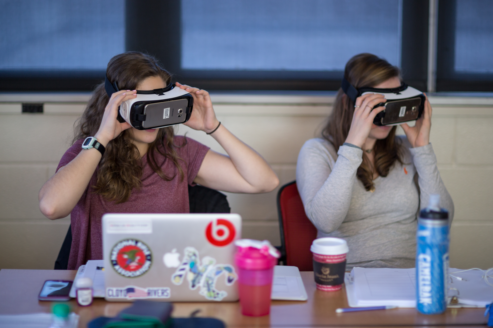 Students wear virtual reality headsets.