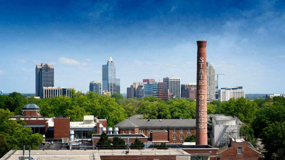 Downtown Raleigh skyline, framed by the State College smoke stack. Photo by Marc Hall.