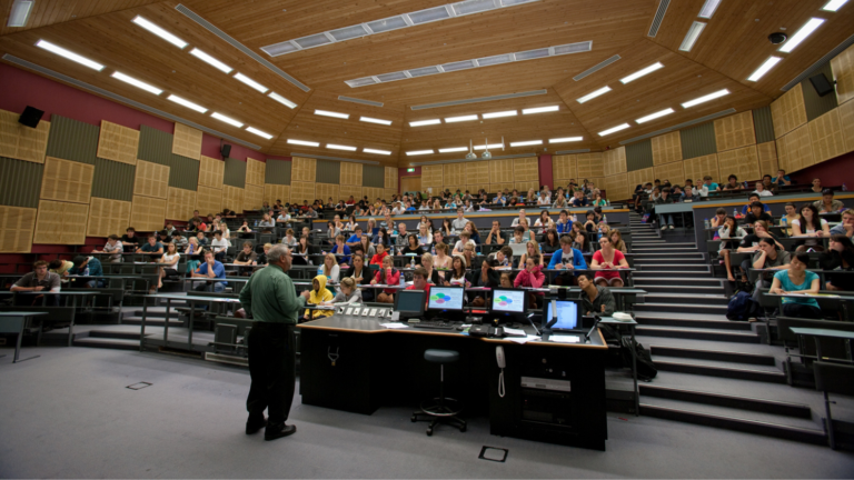 Professor faces a full lecture hall.