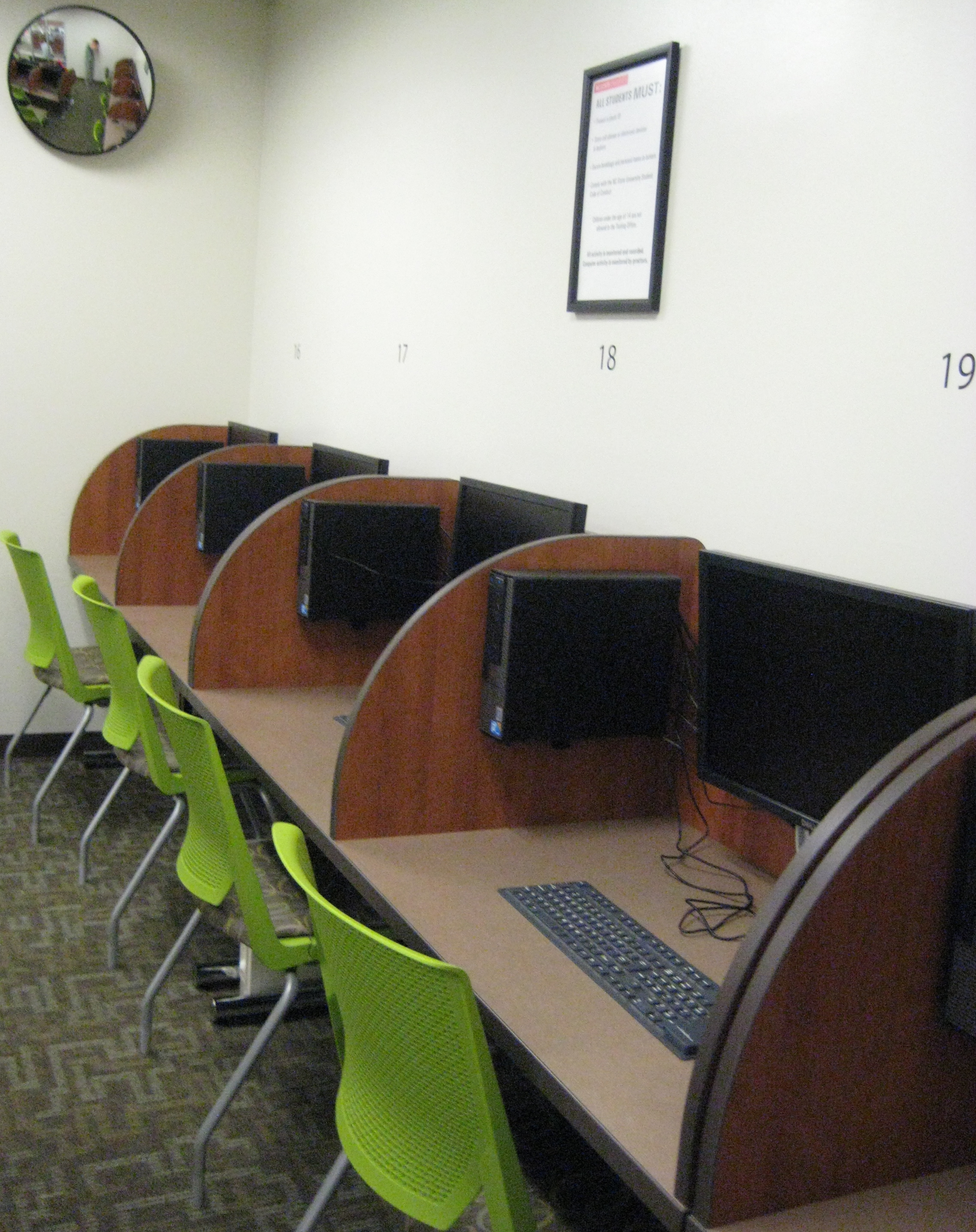 Computers are mounted to the station walls to maximize available desk space.